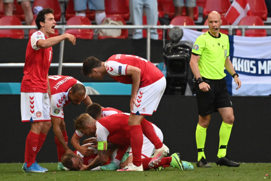 Denmark players help Denmark's midfielder Christian Eriksen after he collapsed during the UEFA EURO 2020 Group B football match between Denmark and Finland at the Parken Stadium in Copenhagen on June 12, 2021. (Photo by Jonathan NACKSTRAND / various sources / AFP) (Photo by JONATHAN NACKSTRAND/AFP via Getty Images)