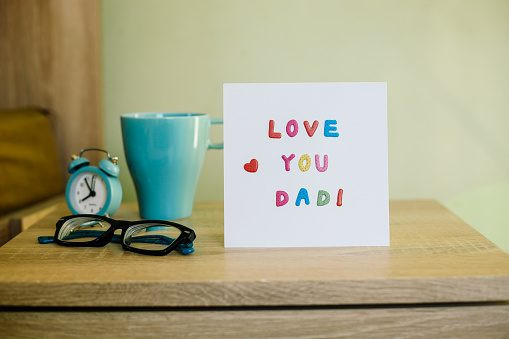 Greeting Card for Happy Father's Day next to a mug, a pair of glasses and a clock