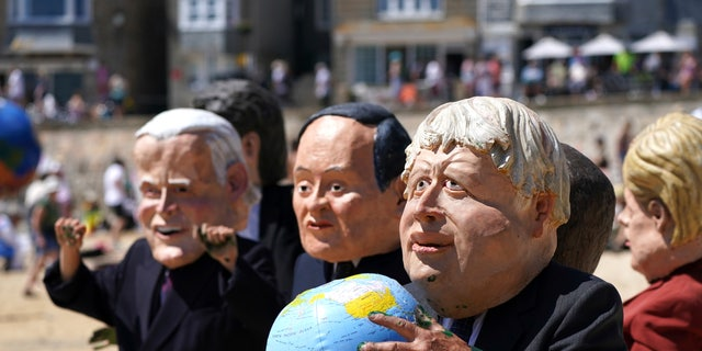 Protestors wearing giant heads portraying G7 leaders participate in a demonstration on a beach outside the G7 meeting in St. Ives, Cornwall, England, Sunday, June 13, 2021. Leaders of the G7 wrap up three days of meetings in Carbis Bay Sunday, in which they discussed such topics as COVID-19, climate, foreign policy and the economy. Leaders portrayed from left, U.S. President Joe Biden, Japan's Prime Minister Yoshihide Suga, British Prime Minister Boris Johnson and German Chancellor Angela Merkel. (AP Photo/Jon Super)