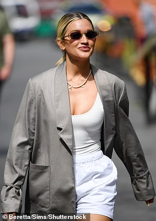Style: The Pussycat Dolls star, 39, cut a typically trendy figure for the day, donning a large grey blazer she wore with white shorts