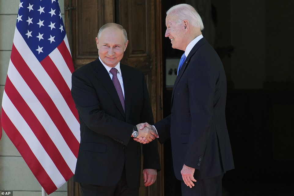 Putin smiles with Biden as the pair shake hands ahead of their highly-anticipated summit to address failing relations