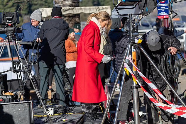 Looking cosy: She rugged up in a long red coat with a cream scarf and matching gloves