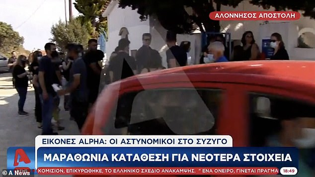 Babis can be seen bottom right, sitting in the back of a car as he is driven away from the memorial to an eight-hour police interrogation where he confessed to the killing