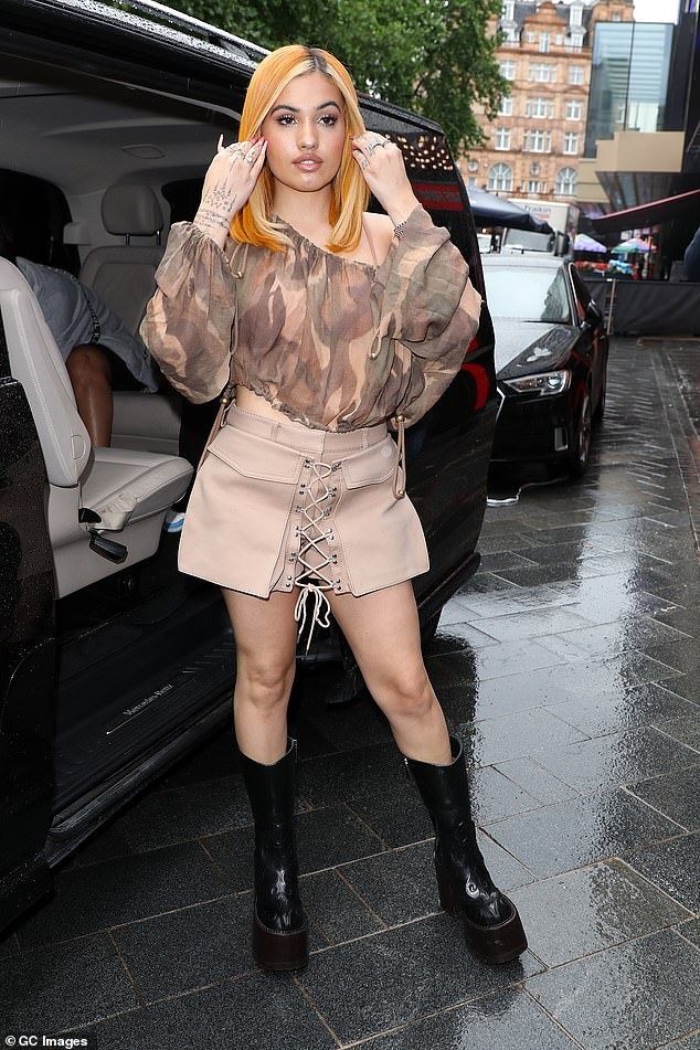Confident:She completed the look with a pair of chunky black shiny boots that were perfect for the rainy London weather