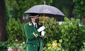 A members of staff shields under an umbrellas during day four of Royal Ascot.