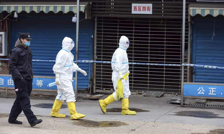 Workers in protective gear at the Huanan seafood market on 27 January 2020