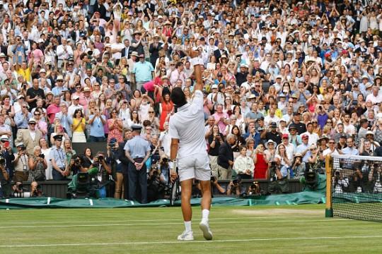 Novak Djokovic raising his fist to the sky after winning the Wimbledon Tennis Championships 2019