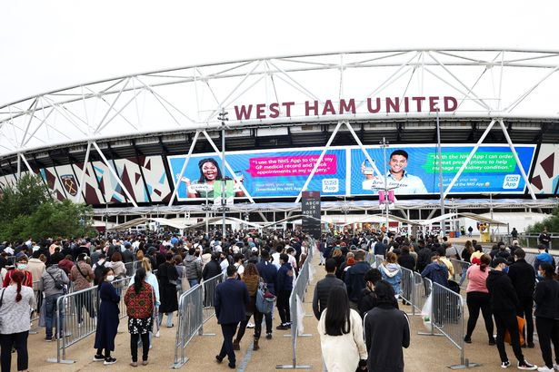 People queue outside a mass vaccination centre for those aged 18 and over at the London Stadium