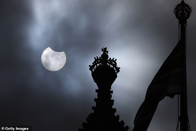 During the event, about 30 percent of the sun was blocked out in Scotland, 20 percent in southern England and as much as 70 percent over Eastern US states. Pictured is thepartial solar eclipse is seen over the Houses of Parliament on June 10 in London, England