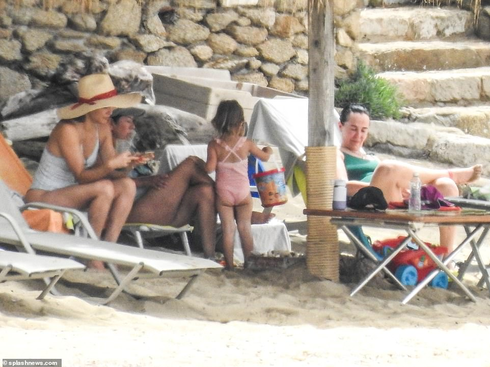 Cooling down: Hudson appeared to be glancing through her phone as she sat in the shade with her pals