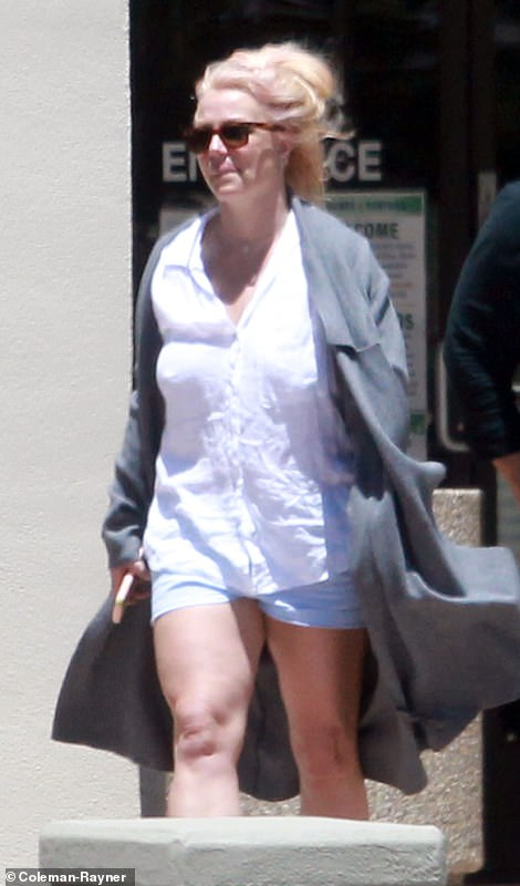 Connected: Britney strolled with her cellphone in hand