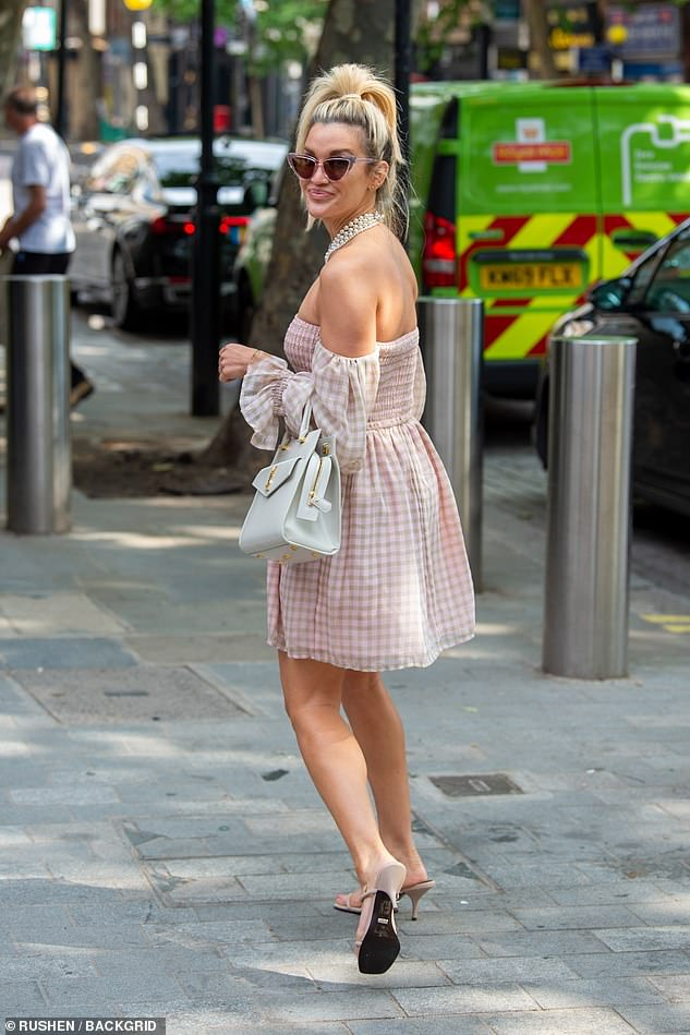Designer garb: She added a boost to her leggy frame with pink strappy sandals and complemented the look with a white YSL handbag