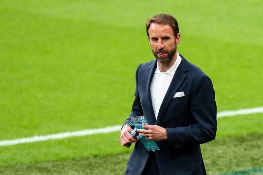 England manager Gareth Southgate in a suit and white shirt walking pitch side.