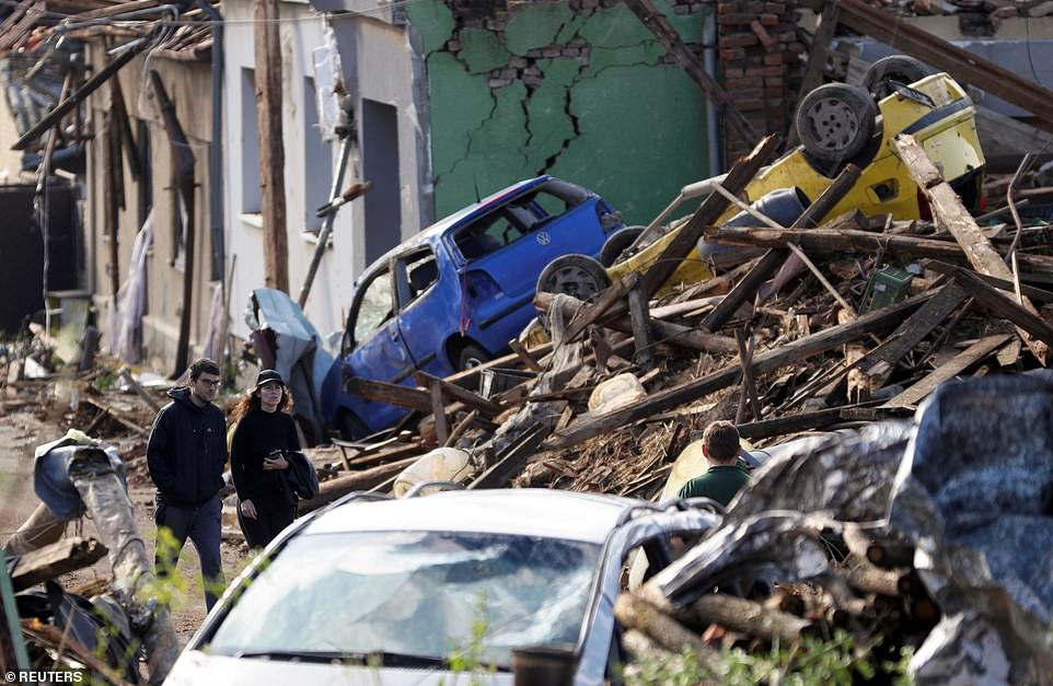 People walk among debris of damaged houses and cars in the aftermath of a rare tornado that struck in Mikulcice village