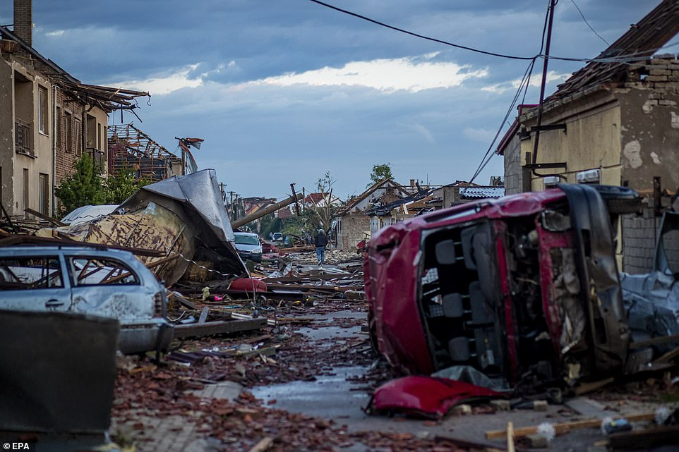'War zone': The streets resembled a battlefield after powerful winds smashed out windows, overturned cars and levelled buildings