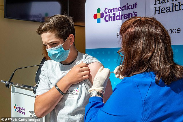 The CDC's COVID-19 Vaccine Safety Technical Work Group said Wednesday that there is a 'likely link' between rare heart inflammation in young males and vaccines. Pictured: Max Zito, age 13, is inoculated by Nurse Karen Pagliaro at Hartford Healthcares mass vaccination center at the Connecticut Convention Center in Hartford, Connecticut, May 13