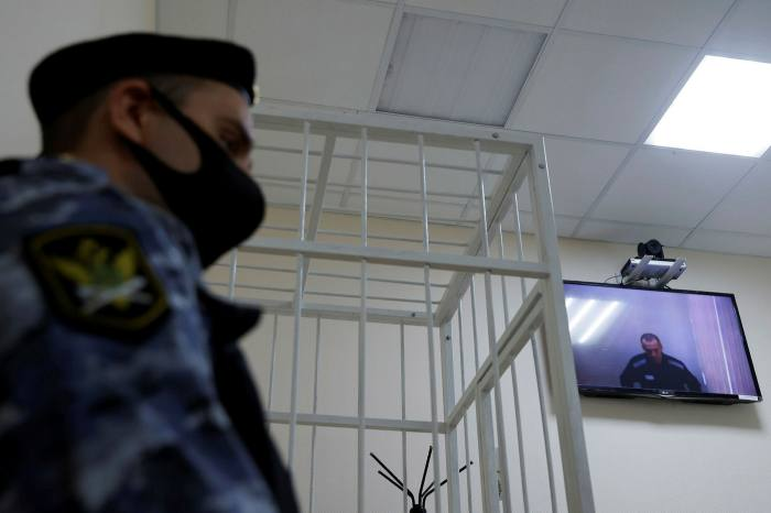 Jailed opposition leader Alexei Navalny is seen on a screen via a video link during court hearing in Russia