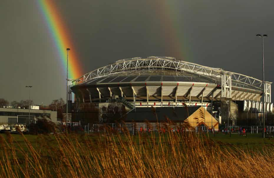 A view outside the stadium as a rainbow is seen in the distance.