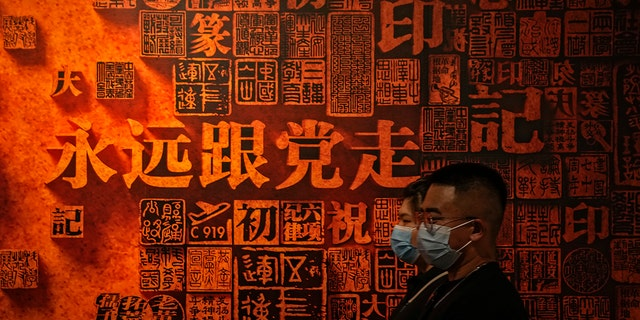 """A couple wearing face masks to help curb the spread of the coronavirus walk by a display board with the words """"Always follow the party"""" on display an exhibition promoting China's achievement under communist party from 1921 to 2021, in Beijing, Sunday, June 20, 2021. (AP Photo/Andy Wong)"""