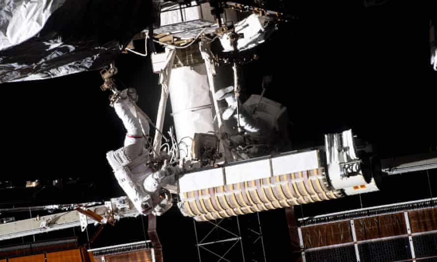 Thomas Pesquet (L) of the European Space Agency is attached to an articulating portable foot restraint on the end of the Canadarm2 robotic arm carrying new roll out solar arrays towards the International Space Station's P-6 truss structure, next to US astronaut Shane Kimbrough.
