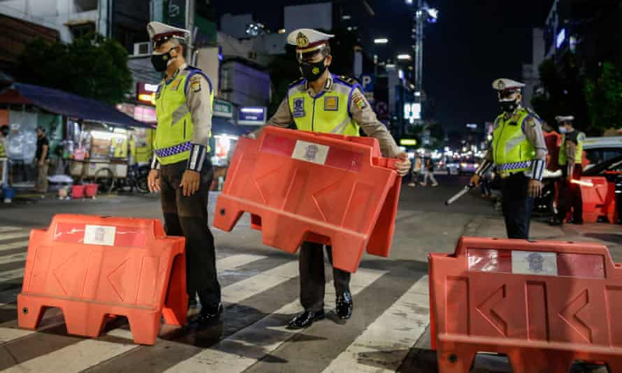 Police officers install road barricades as they close the road following the government's decision to impose tighter social restrictions amid the rising number of Covid-19 infections in Jakarta