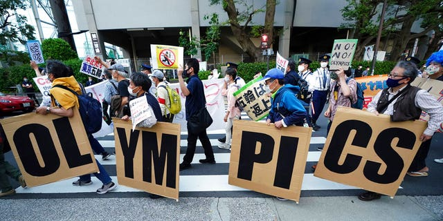 FILE: People who are against the Tokyo 2020 Olympics set to open in July, march to protest around Tokyo's National Stadium during an anti-Olympics demonstration.
