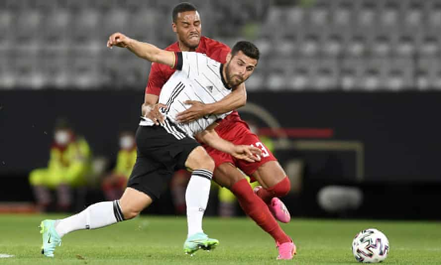 Denmark's Mathias Jørgensen fights for the ball with Germany's Kevin Volland