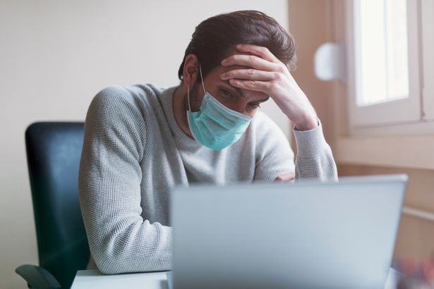 Man with medical mask, working from home and feeling a headache