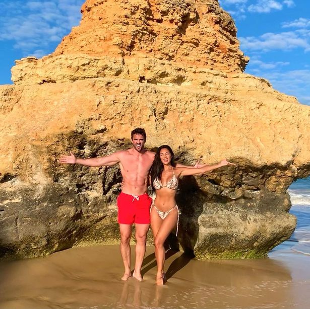 The couple posed happily in the shallow water