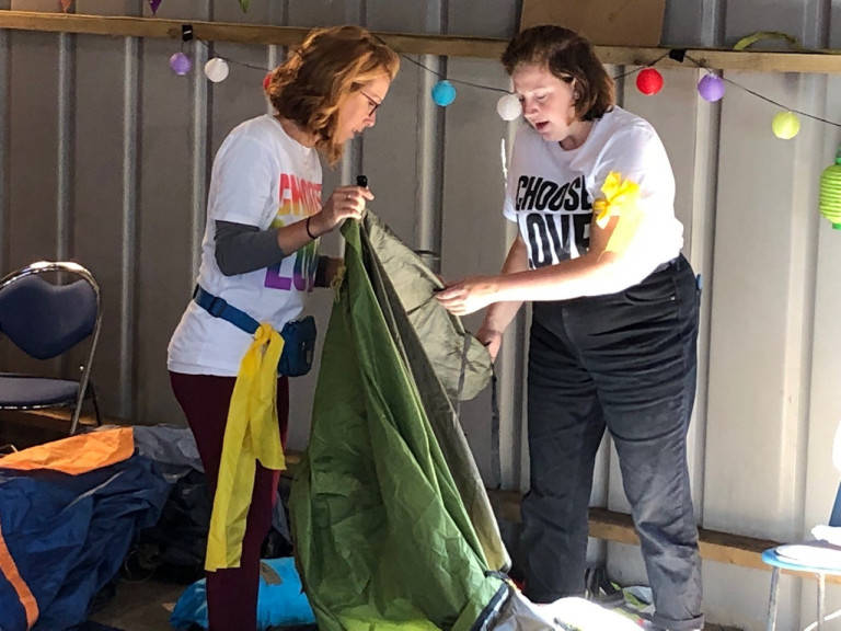 Sol Escabar holding a sleeping bag in a warehouse, next to a woman in a Choose Love t-shirt