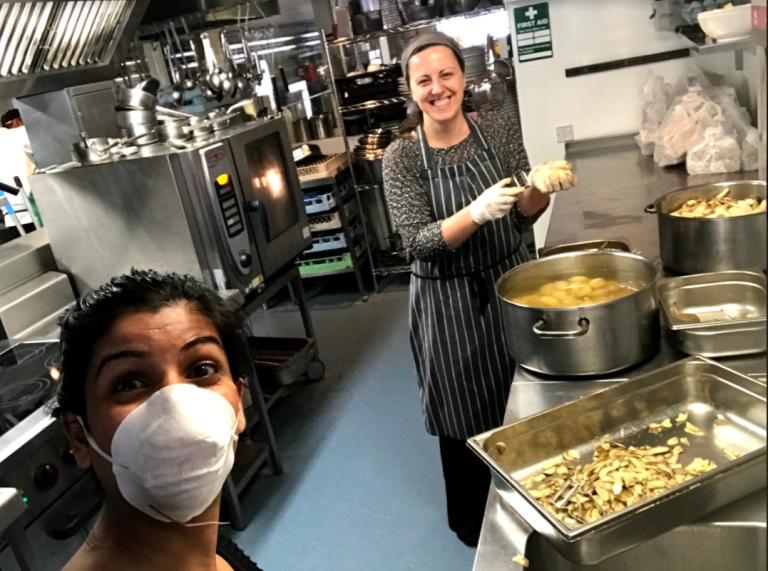 Libby Brewster in a big kitchen peeling potatoes in front of a big pot. Next to her is a woman in a face mask