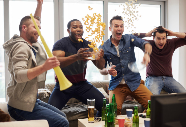 Group of men watching sport event on television celebrating