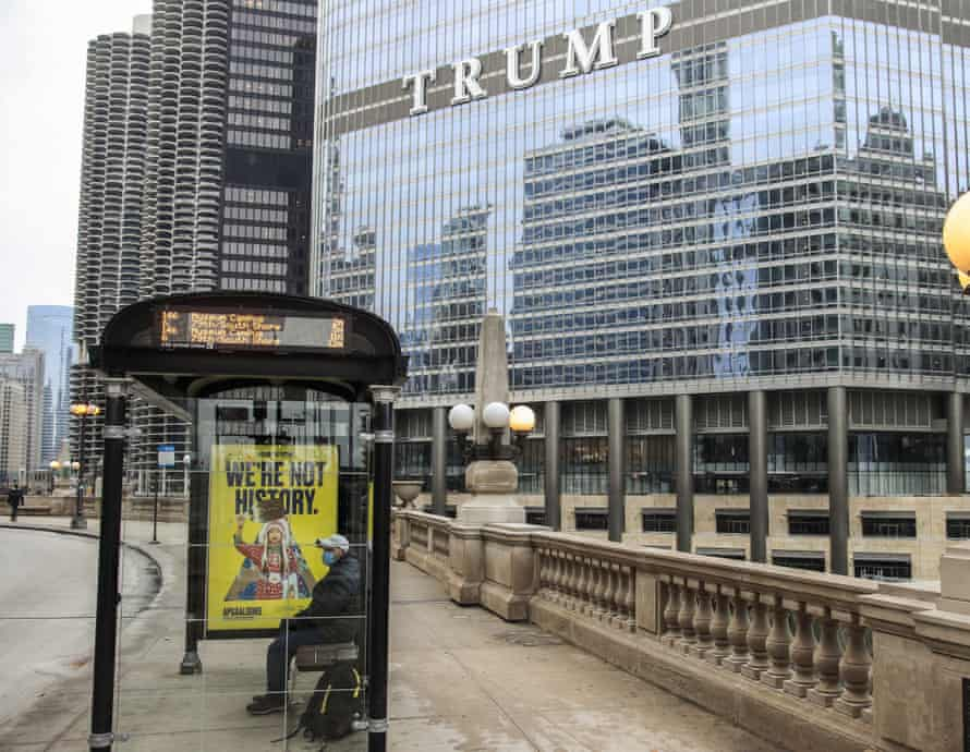 A man sits in a covered bus shelter near the Trump International Hotel & Tower in Chicago, Illinois, in January.