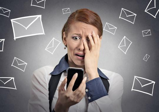 Woman looking at mobile phone behind fingers in disbelief