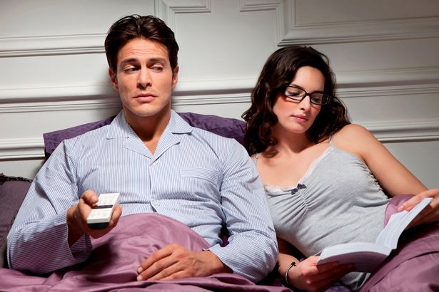 A couple in bed. The man is watching television and the woman is reading a book.