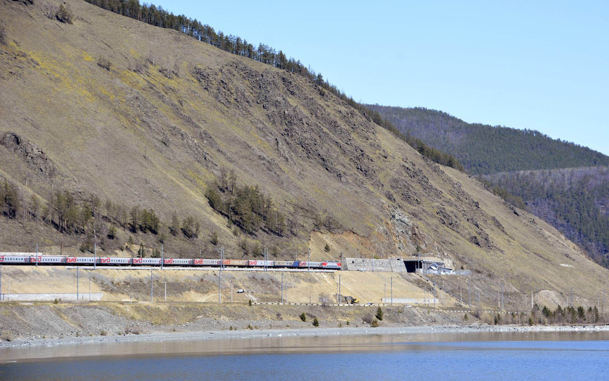 A photo taken on May 28 shows a passenger train running on the Baikal-Amur Mainline on the shores of Lake Baikal in Severobaykalsk, Russia. | KYODO