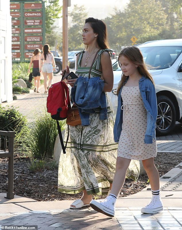 Devoted mama: Jessica carries her kids' bags as they make their way to dinner