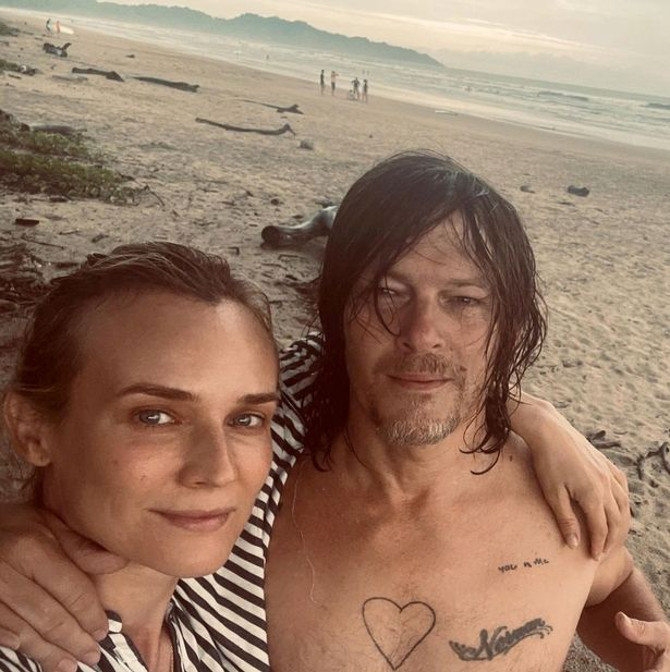Diane Kruger and Norman Reedus pose for a selfie on a beach