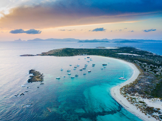 Aerial landscape view of Espalmador and Ibiza during sunset with sailboats anchored.