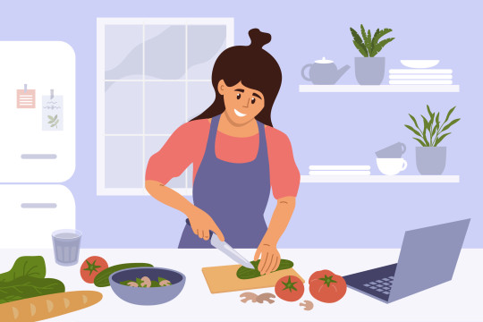 Smiling woman in kitchen watching culinary video blog and cooking healthy meals