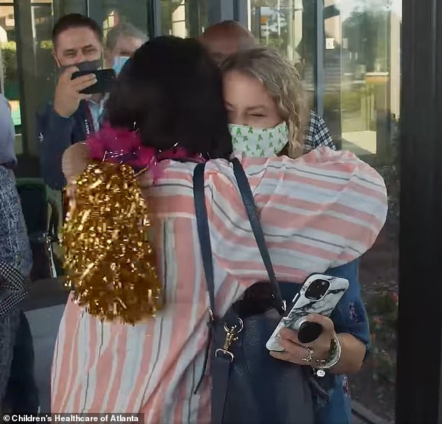 Tia and Susan hug as they returned to work for the first time since their surgeries in May