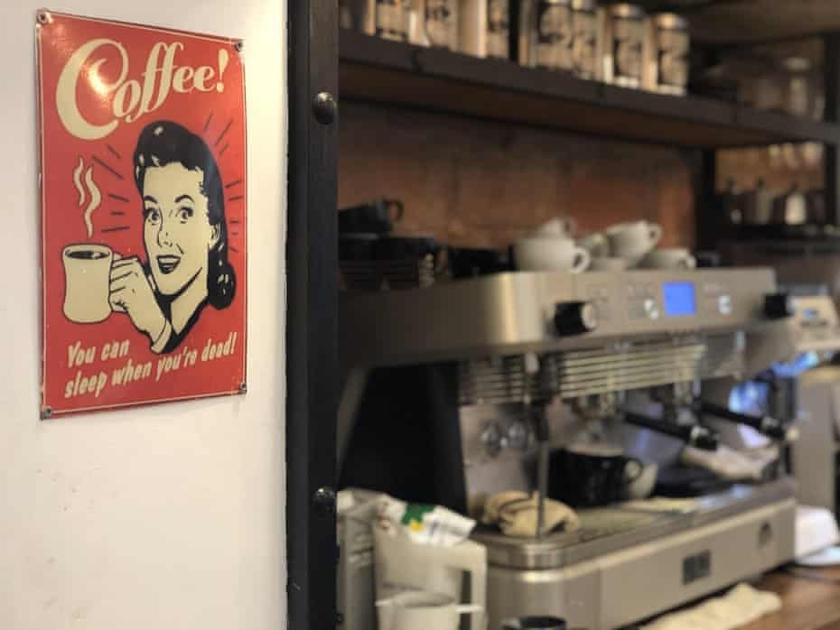 a sign reading 'coffee - you can sleep when you're dead' close to a coffee machine