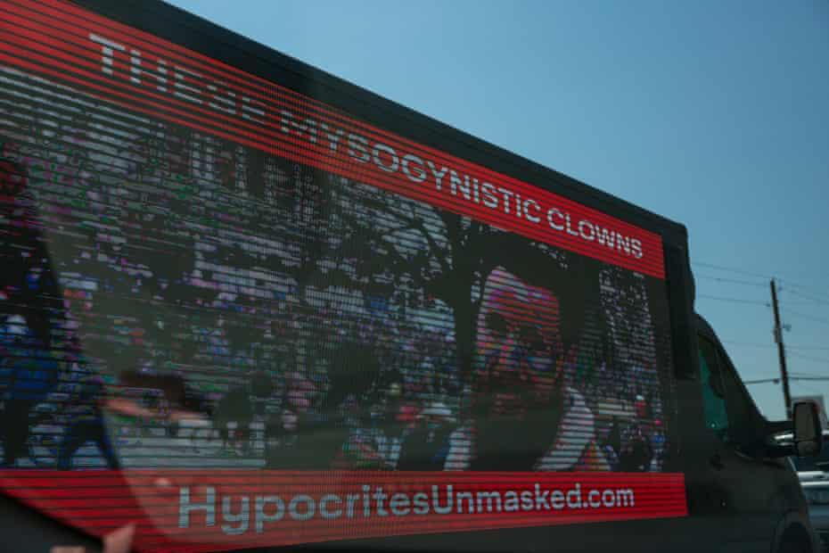 """image on side of truck says """"these mysogynist clowns - hypocrites unmasked dot com"""""""