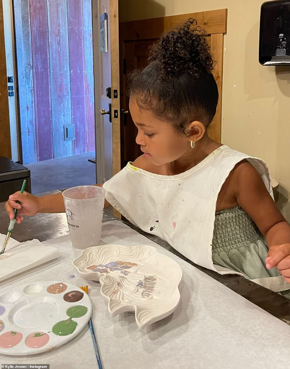 Budding artist: Later in the day, Stormi was pictured painting a ceramic white bowl as the young family enjoyed their lakeside break