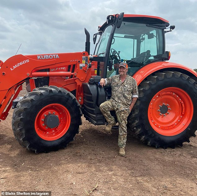 All his: Blake posing in camo clothing next to his red Kubota tractor on his land