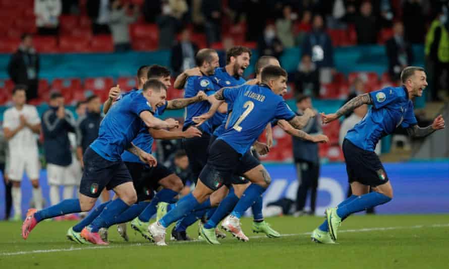 Italy players celebrate as Jorginho's penalty beats Unai Simón to seal victory.