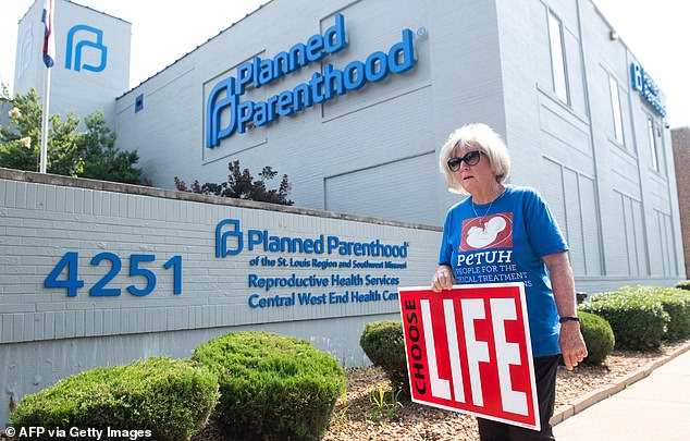 Abortion is a hot button issue in the United States, and Planned Parenthood's federal funding has become a key battleground. Pictured: a women participates in a pro-life protest outside of a Planned Parenthood office in St Louis, Missouri