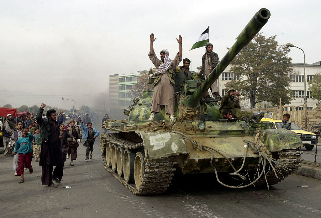Coalition-backed Northern Alliance fighters ride tanks into Kabul as the Taliban retreat
