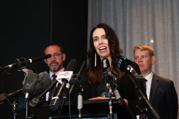 PM Ardern flanked by her Covid-19 response minister Chris Hipkins (back right)
