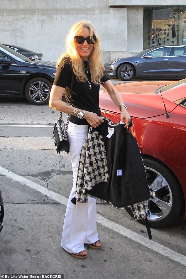 Stylish ensemble: The former model was glowing in the evening sun and showed off her slender legs wearing white flared jeans and a black T-shirt